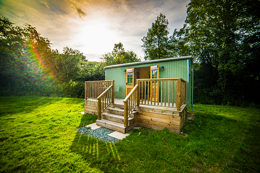 Shepherds-hut-in-sun,-camping,-glamping,-luxury